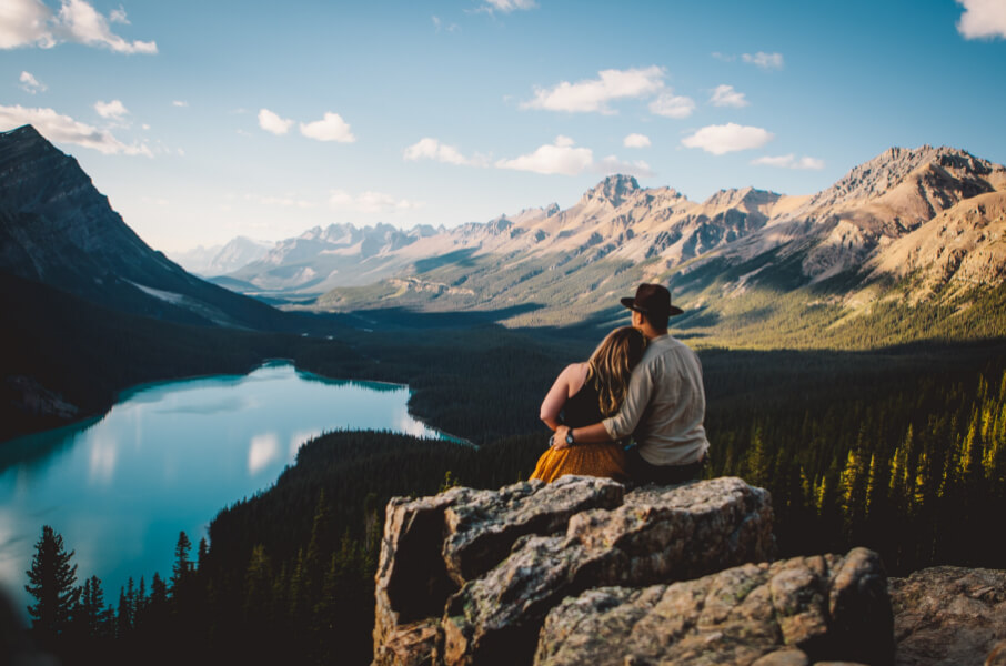 Couple sitting on a mountain looking at a lake